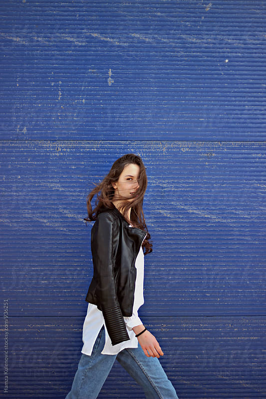Girl walking next to blue garage doors by Hamza Kulenović for Stocksy United