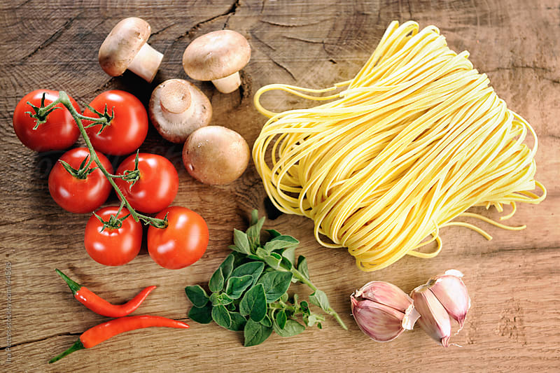 Food: Pasta ingredients,  fresh Tagliatelle, garlic, mushrooms, oregano, tomatoes and oregano by Ina Peters for Stocksy United
