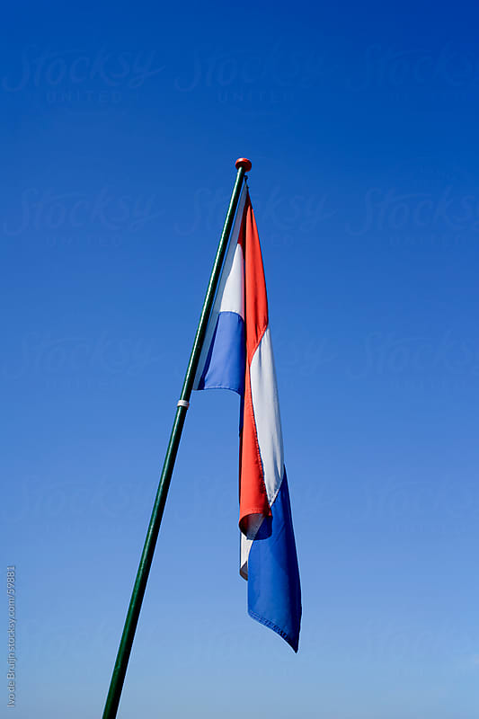 A  dutch flag in a windless sky, in the Netherlands by Ivo de Bruijn for Stocksy United