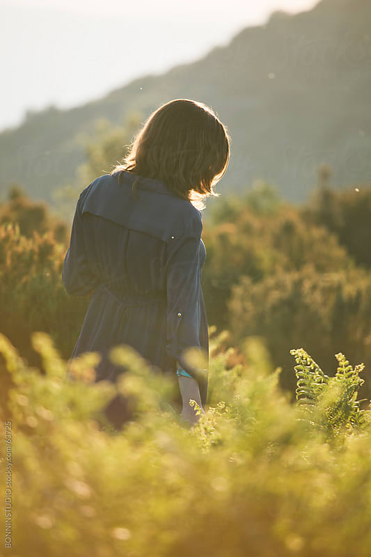 Back view of young woman on sunset landscape. by BONNINSTUDIO for Stocksy United