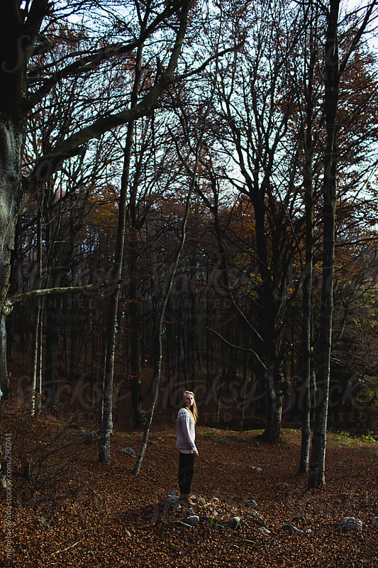 Alone girl standing in the woods by michela ravasio for Stocksy United