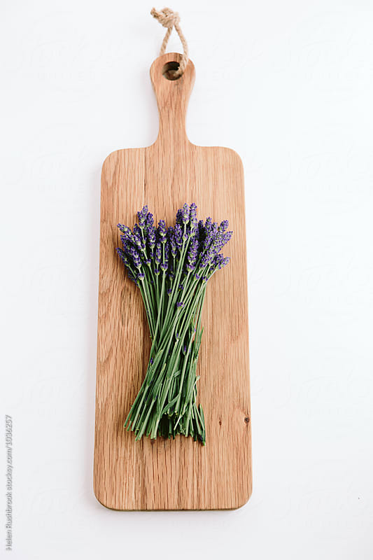 Cut lavender flowers on a wooden board. by Helen Rushbrook for Stocksy United