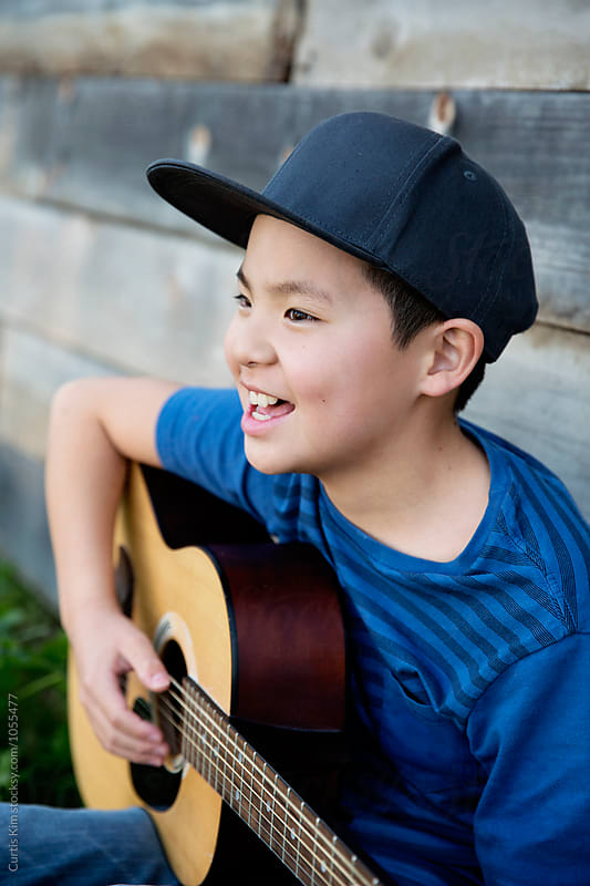 Asian boy singing and playing his guitar by Curtis Kim for Stocksy United