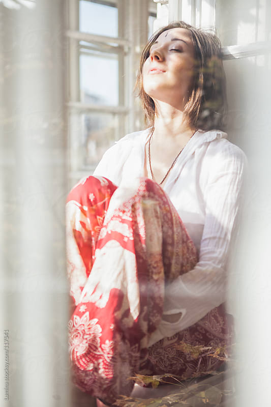 Smiling Woman Sitting by the Window by Lumina for Stocksy United