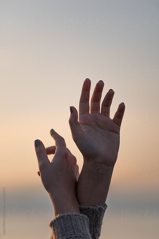 Famale hands raised against the sky at sunset by Luca Pierro for Stocksy United