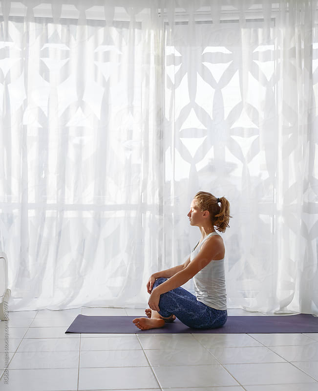 Woman doing yoga in front of the window by RG&B Images for Stocksy United