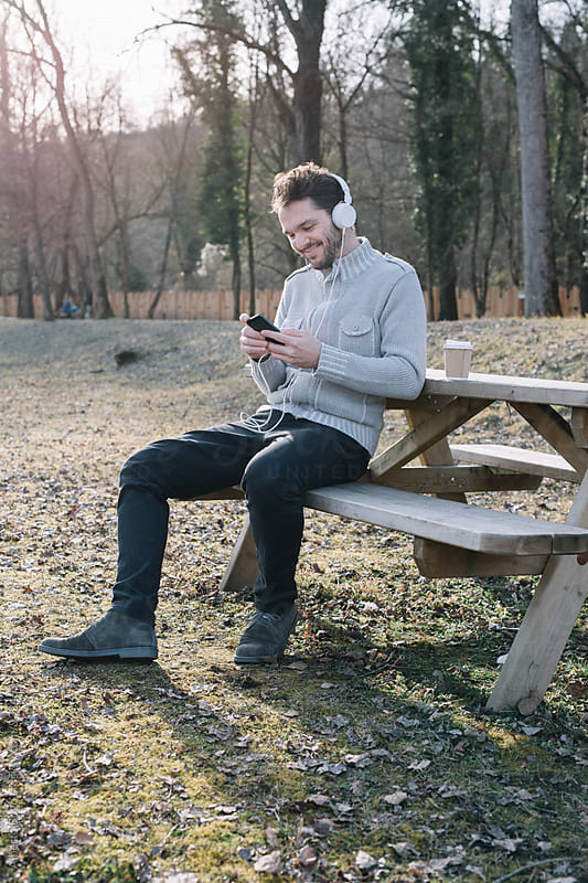 Bearded man listening to music in autumnal park by Alberto Bogo for Stocksy United