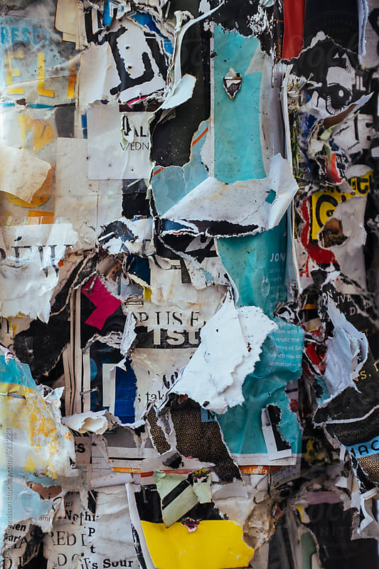 Layers of torn and peeling posters attached to telephone pole, close up by Paul Edmondson for Stocksy United