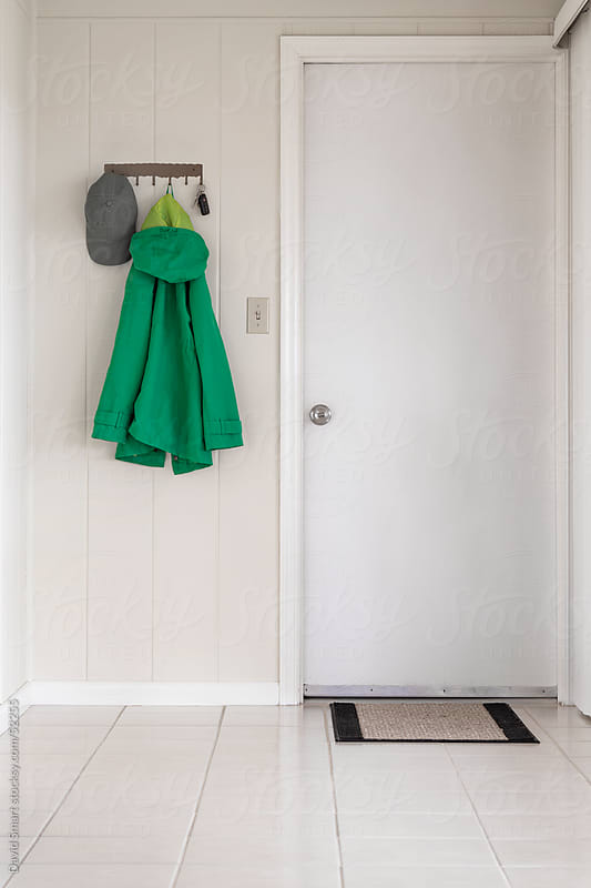 Green jacket, cap and car keys hanging by a door that goes from house to garage. by David Smart for Stocksy United