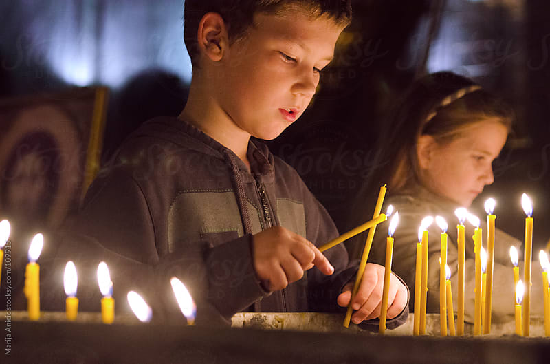 Boy and girl lighting candles in Church by Marija Anicic for Stocksy United