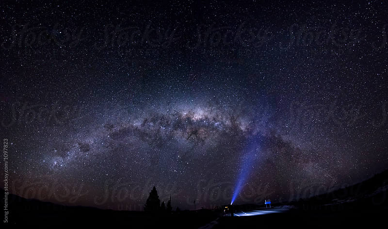 A male adventurer with strong headlamp under the full panorama of the Galaxy by Song Heming for Stocksy United