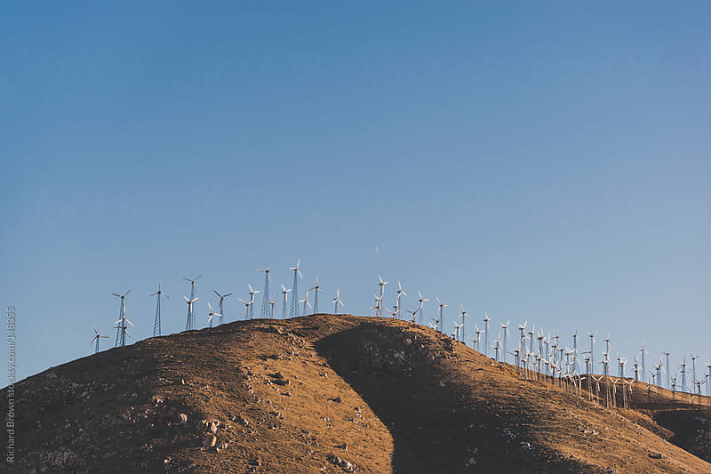 Wind farm and rolling hills by Richard Brown for Stocksy United