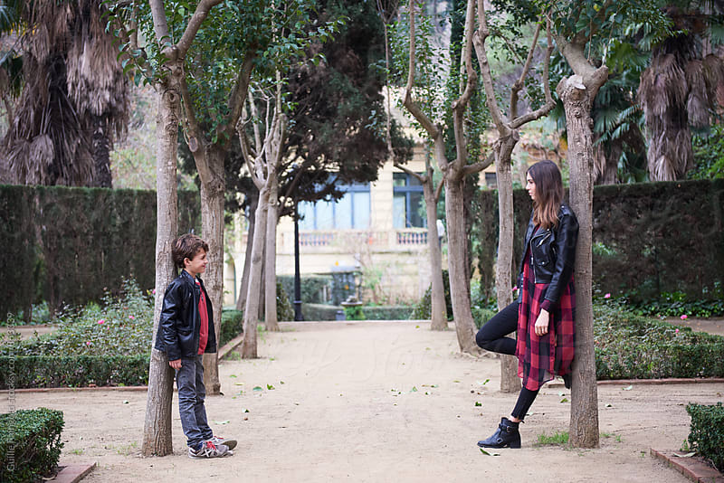 Sister and brother leaning on trees and looking at each other by Guille Faingold for Stocksy United