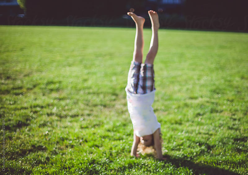 A little girl in a hand stand. by Cherish Bryck for Stocksy United