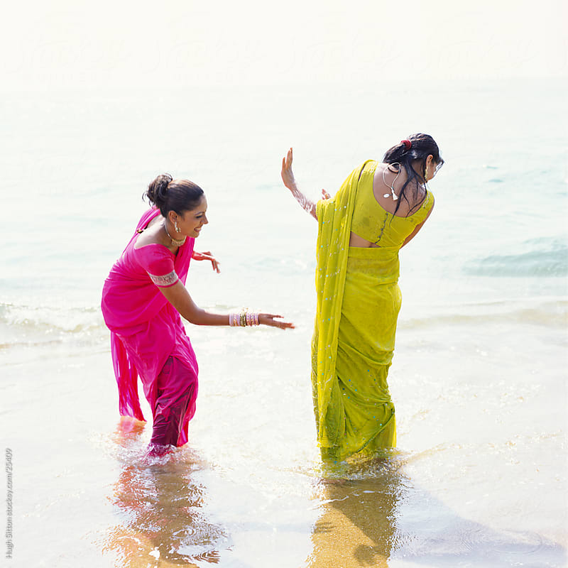 Two Indian women playing in the sea. Mumbai by Hugh Sitton for Stocksy United