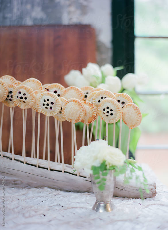 Mini Pie Pops displayed in driftwood stand by Marta Locklear for Stocksy United