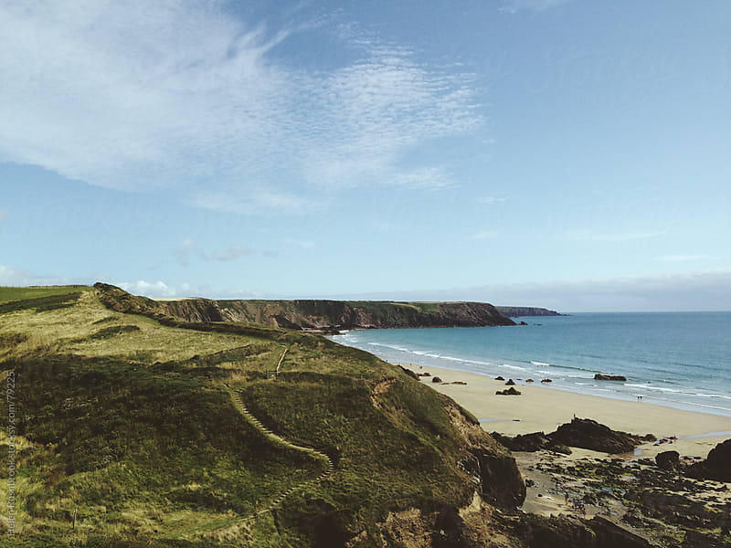 A cliff-top coast path and beach. by Helen Rushbrook for Stocksy United