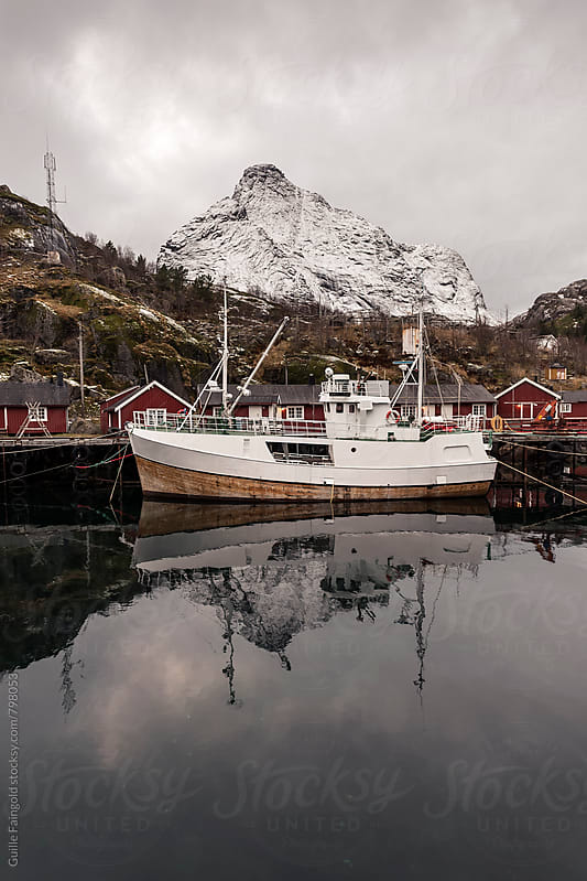 fishing boat on a norway harbor by Guille Faingold for Stocksy United