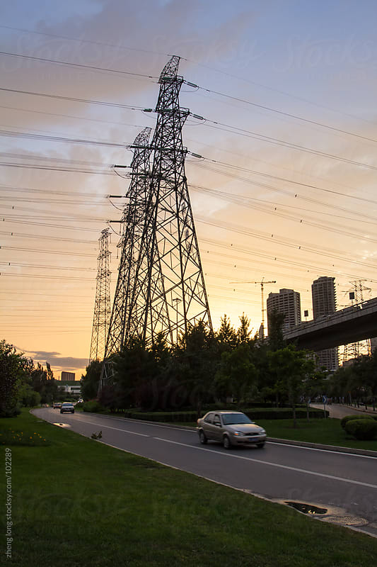 High voltage tower in city at dusk,Beijing by zheng long for Stocksy United