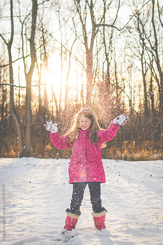 Snow falling on girl in sunlight by Lindsay Crandall for Stocksy United