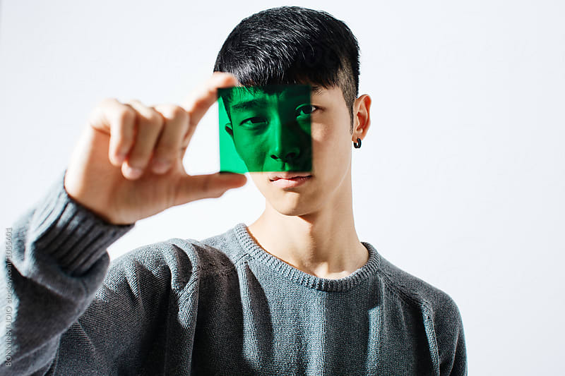 Portrait of an asian man looking through green glass. by BONNINSTUDIO for Stocksy United