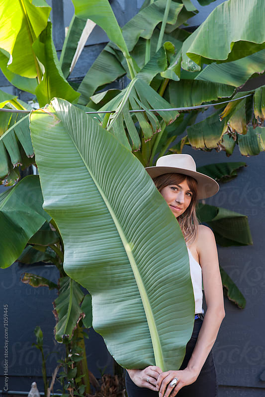 Woman With A Large Banana Leaf by Carey Haider for Stocksy United