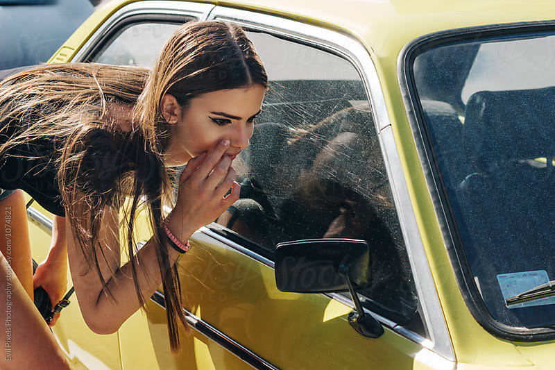 Young female model looking her self at rearview mirror of yellow oldtimer by Evil Pixels Photography for Stocksy United