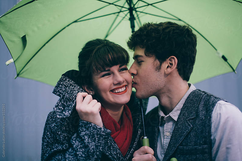 Couple Kissing in the Rain by Gabrielle Lutze for Stocksy United
