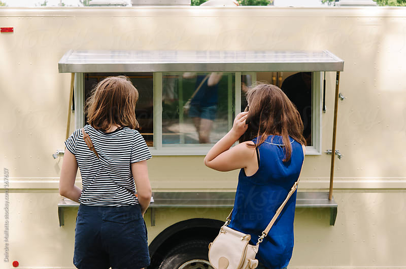 teen girls buying lunch at a food truck by Deirdre Malfatto for Stocksy United