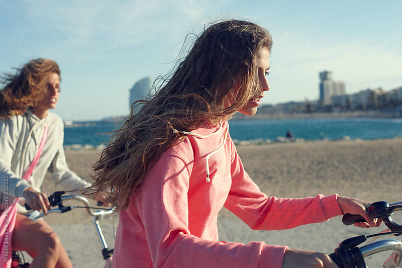 Two young girls  riding a bike by the beach of Barcelona city by Miquel Llonch for Stocksy United