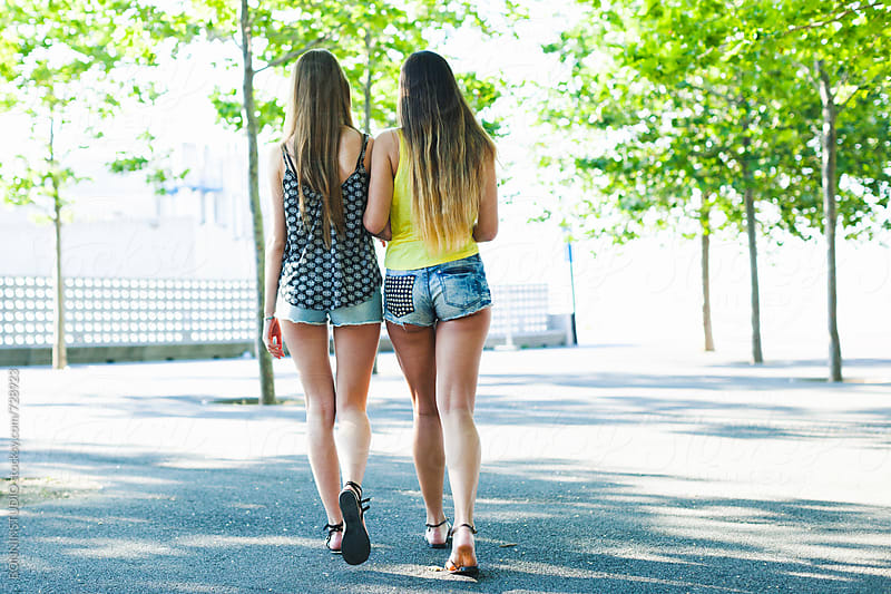 Back view of a two female friends walking in the park on summer. by BONNINSTUDIO for Stocksy United