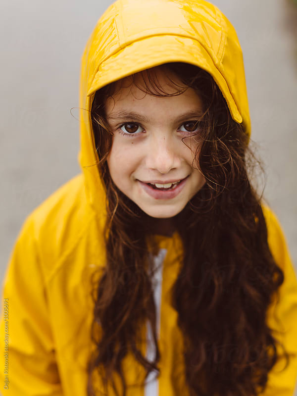Smiling girl with yellow raincoat. by Dejan Ristovski for Stocksy United