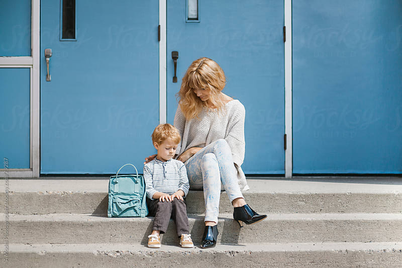 Mother and son sitting on the stairs in front of the school by Ania Boniecka for Stocksy United