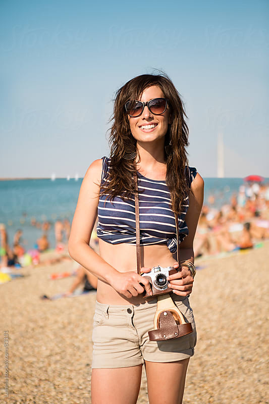 Smiling Woman Taking Photos on the Beach by Lumina for Stocksy United