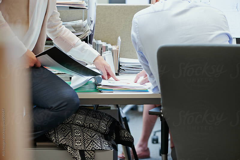 Close image of business team meeting sitting at a desk by Aila Images for Stocksy United