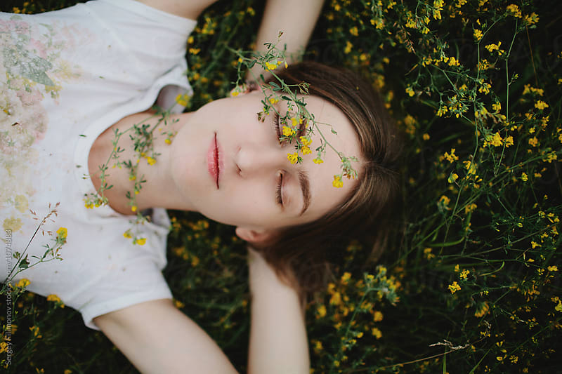 A cute girl lie down behind yellow flowers by Sergey Filimonov for Stocksy United