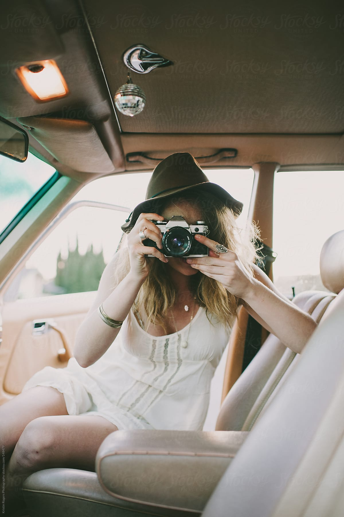 Pretty stylish girl playing with camera inside of old car by