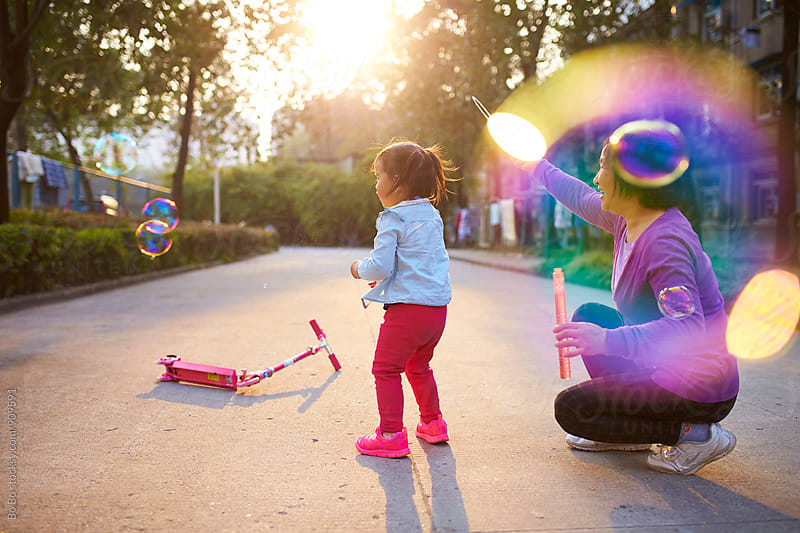 little asian girl playing bubble with her grandmother outdoor by Bo Bo for Stocksy United
