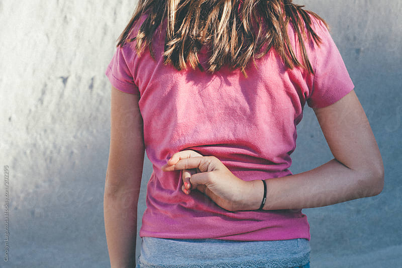 Young teen (tween) girl crossing her fingers behind her back by Carolyn Lagattuta for Stocksy United