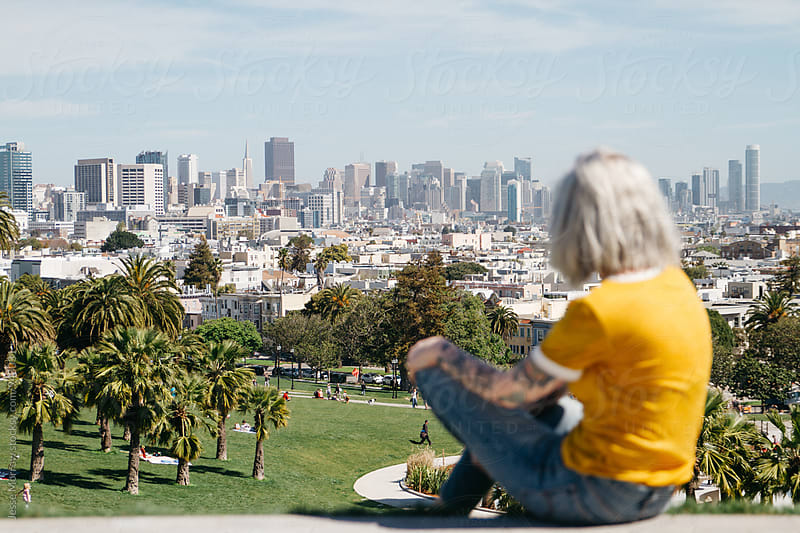 young woman in san francisco park looking out over city buildings by Jesse Morrow for Stocksy United