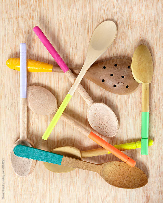 Whimsical arrangement of wooden spoons dipped in bright colors on a light wood background by Sherry Heck for Stocksy United