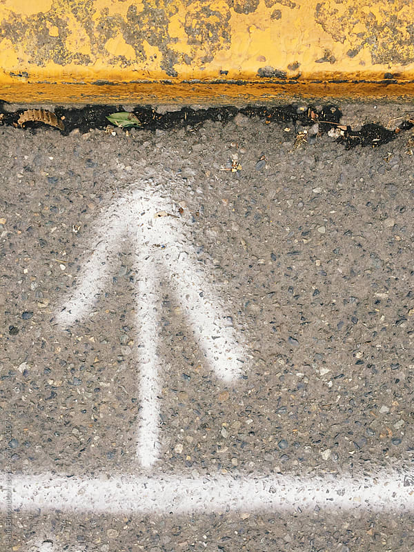 Spray painted white arrow on street with yellow curb by Paul Edmondson for Stocksy United