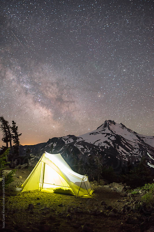 Tent in front of Mt Jefferson with starry night sky by Isaac Lane Koval for Stocksy United