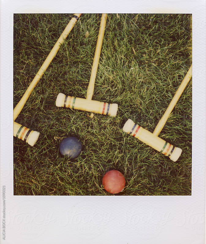 Croquet Mallets And Balls Laying In Summer Grass On Expired Polaroid Film by ALICIA BOCK for Stocksy United