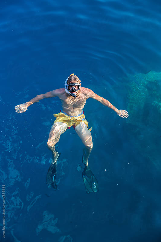Handsome young man snorkeling in deep blue ocean water by Jovo Jovanovic for Stocksy United