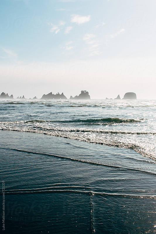 A Gentle Blue Ocean Tide Rolls Over The Shore  by Luke Mattson for Stocksy United