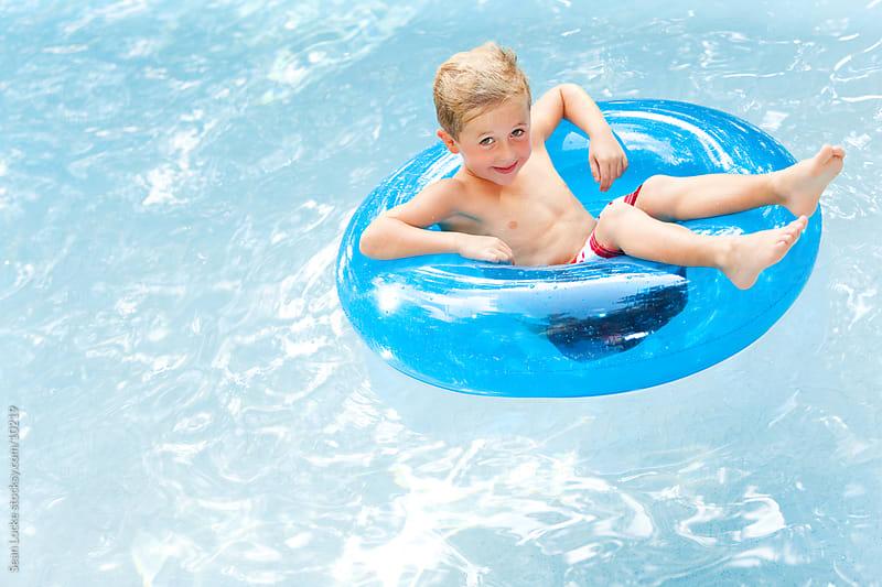 Swimming: Cute Little Boy Floating in Tube by Sean Locke for Stocksy United