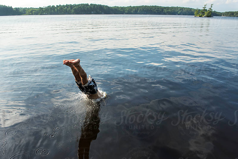 Man is halfway in the water as he dives into a lake by Cara Dolan for Stocksy United