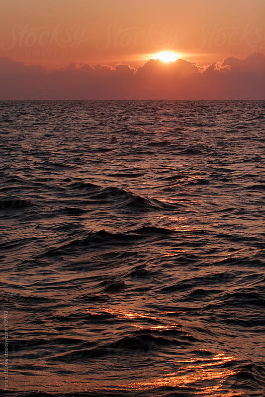 Sunset behind glowing clouds above sea horizon by Ferenc Boros for Stocksy United