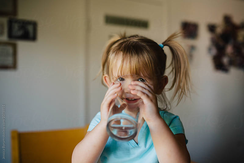Toddler child looking at the camera while taking a drink of water from a big glass of water. by Jessica Byrum for Stocksy United